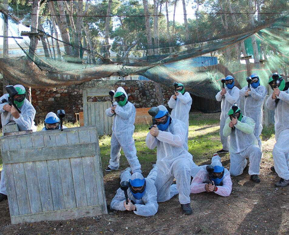 Group of young people playing paintball